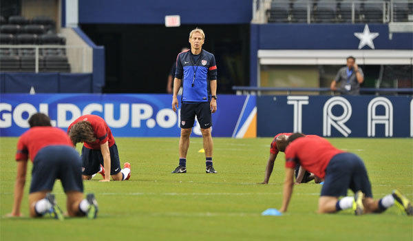 U.S. Coach Juergen Klinsmann watches his players stretch during a Gold Cup training session at Cowboys Stadium on Tuesday.
