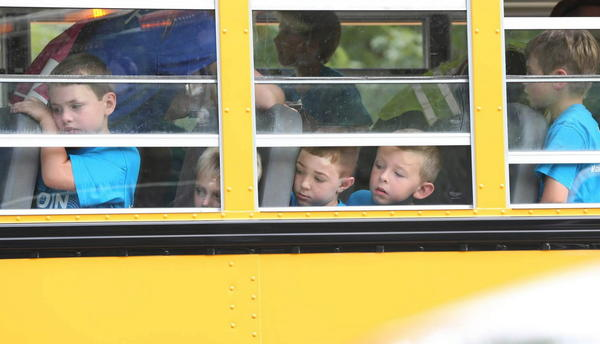 Children watch Fox Lake Fire Officials at the scene of an accident involving the school bus and a sedan at Devlin Road and Rt. 59 in Fox Lake, Ill.