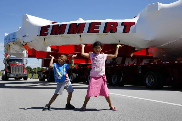 "Eli Piotrowski and his sister Maddie, of Downers Grove, ""hold up"" the 50-foot-wide electromagnet headed to Fermilab on Wednesday in a Bolingbrook parking lot."