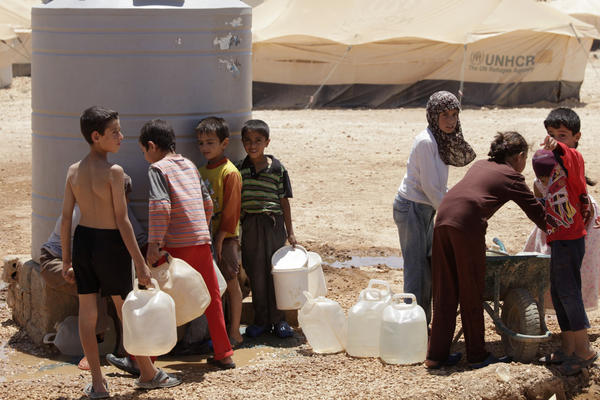 Syrian refugees fill up their water jugs at the Zaatari refugee camp near the Syrian border in Mafraq, Jordan. Zaatari is home to about 120,000 Syrians.