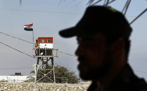 A policeman, foreground, with the Hamas militant group stands guard in the southern Gaza Strip as an Egyptian soldier watches from the other side of the border. Egyptian security officials say Hamas has dispatched militants to the Sinai Peninsula.