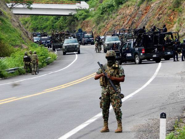 Federal security personnel stand guard on a road where alleged drug traffickers attacked federal police officers near Arteaga, in Mexico's Michoacan state, killing two.