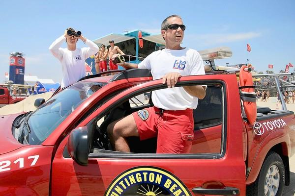 Marine Safety Officer Matt Karl, center, and Recurrent Ocean Lifeguard Ericka Lorenz, left, survey the crowd along the south side of the pier on Monday during the U.S. Open of Surfing in Huntington Beach.