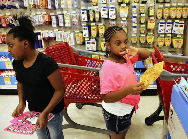Jada Clother, 9, left, and cousin Lashea Watson, 10, shop for school at a Target store Wednesday in Chicago.