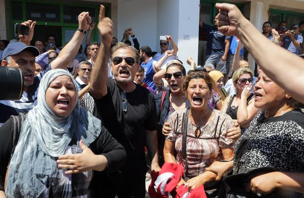 Tunisians shout slogans as they protest near a hospital where opposition politician Mohammed Brahmi was taken following his assassination.
