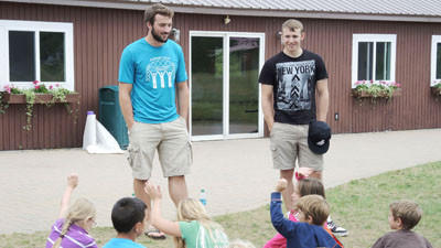 Parker Adams (standing, left) and Zach Spehar (standing, right) speak to participants in the YMCA of Northern Michigan's summer day camp at Camp Pet-O-Se-Ga.
