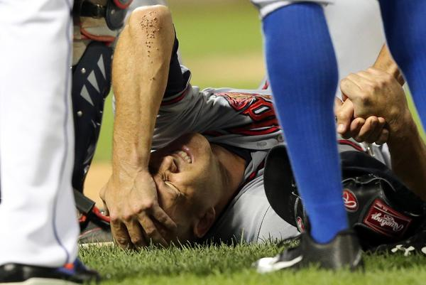 Atlanta Braves pitcher Tim Hudson reacts after being injured in a collision at first base with New York Mets left fielder Eric Young Jr.