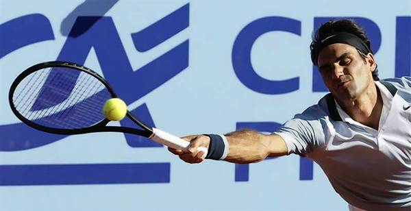 Switzerland's Roger Federer returns the ball to Germany's Daniel Brands during their Swiss Open second round tennis match in Gstaad.