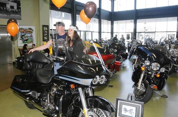 Robert Shingler and his wife Susan pose for pictures with their new Harley. Harley-Davidson celebrated a milestone - the sale of the iconic manufacturer's four millionth motorcycle at Gator Harley-Davidson in Leesburg.