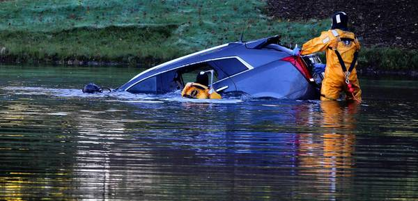 Divers try to gain access to an SUV and its driver after it went into a pond at the Arlington on the Ponds subdivision in Arlington Heights on Thursday.