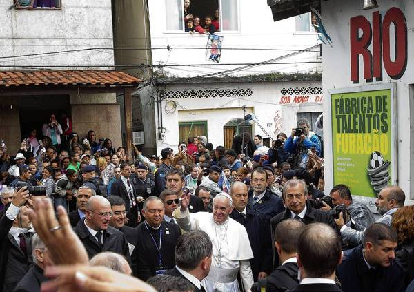 Pope Francis walks through the crowd during his visit to the Rio de Janeiro slum of Varginha.
