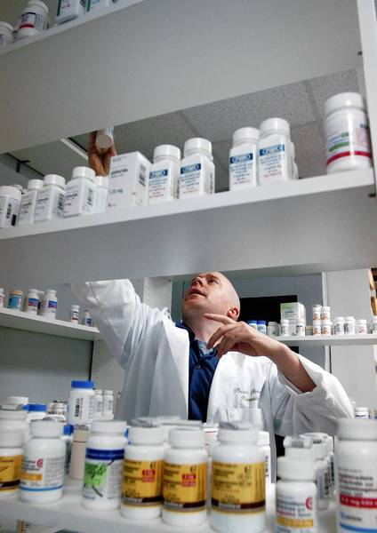 Pharmacists say the National Prescription Savings Network cards do provide a discount for those without insurance, though 75% savings is doubtful. Above, discount pharmacist Howard Brooker in Glenside, Pa., in 2006.