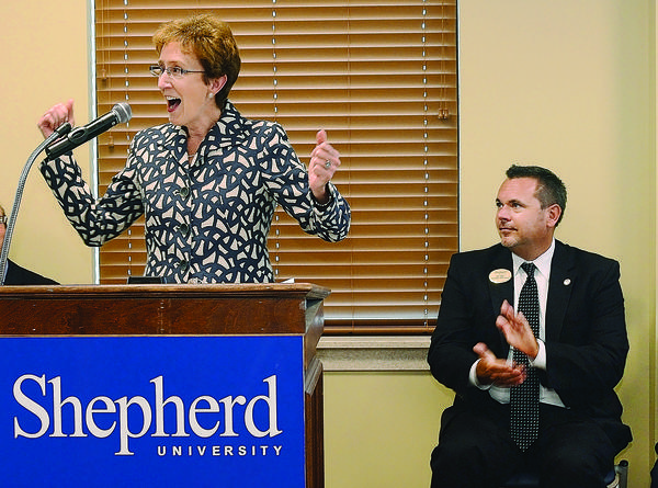 Shepherd University President Suzanne Shipley speaks at a ribbon cutting at the new Shepherd University Martinsburg Center. Looking on is James Klein, director of the center.