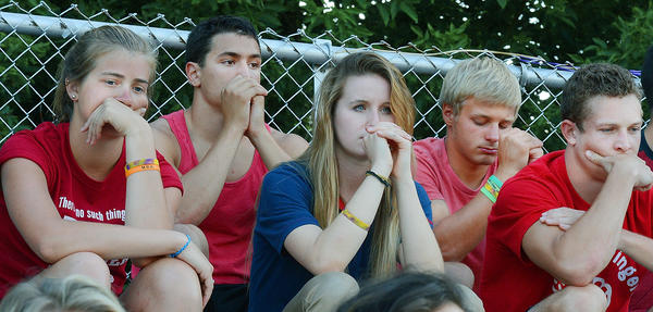 Smithsburg High School classmates of Preston Miller, Emma Zahm, left, Steven Rishell, Caitlyn Wilson, LJ Etter and Zane Gardenhour collect their thoughts as words are spoken about Miller at a prayer vigil at the school's football field Thursday evening.