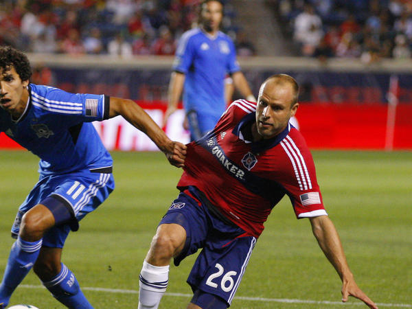 Earthquakes midfielder Mehdi Ballouchy (left) pulls down Fire midfielder Joel Lindpere during the second half at Toyota Park.