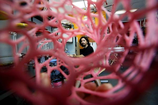 Diego Porqueras, owner of Deezmaker in Pasadena, is visible through one of the plastic objects he made with a 3-D printer.