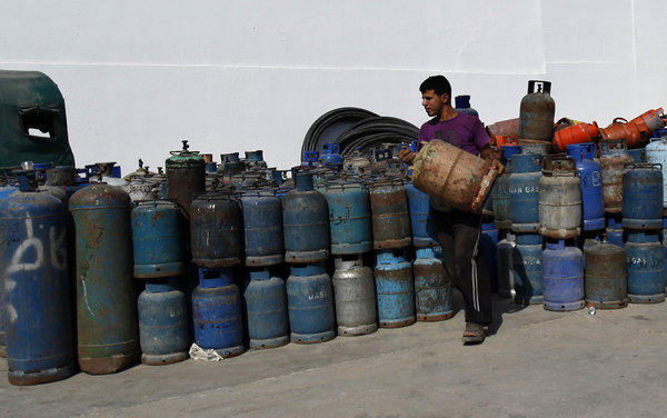 A Palestinian worker carries a cooking gas cylinder in Gaza City this month.