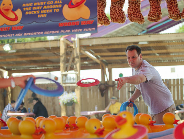 Brad Zint plays Ring A Duck, a carnival game at the Orange County Fair on Wednesday.