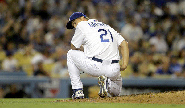 Zack Greinke kneels on the ground after giving up a two-run home run to Reds right fielder Jay Bruce (32) in the sixth inning of the Dodgers' 5-2 loss to Cincinnati on Thursday.