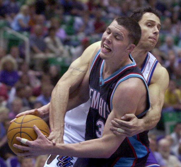 Utah Jazz forward Tom Gugliotta, rear, fouls Memphis Grizzlies guard Mike Miller (33) to keep him from scoring in the first quarter Monday, April 5, 2004, in Salt Lake City. (AP Photo/Douglas C. Pizac)