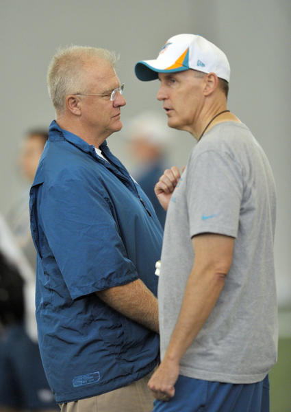 Miami Dolphins offensive coordinator Mike Sherman (left) talks with head coach Joe Philbin (right) during training camp at the Doctors Hospital Training Facility at Nova Southeastern University.