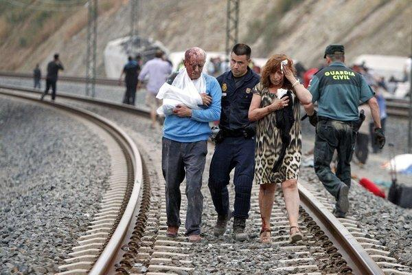 Wounded people are evacuated Wednesday at the site of a train accident in Santiago de Compostela, Spain. Spanish police on Friday detained the driver of the train.