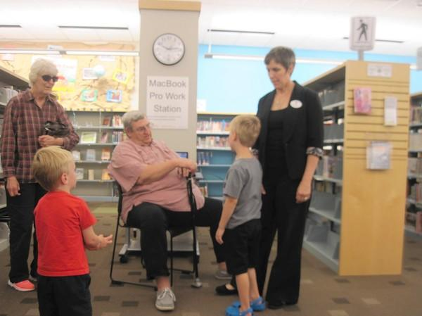 Youth and Young Adults Services Manager Tiffany Verzani, right, chats with guests during her going away party at the Hinsdale Public Library.
