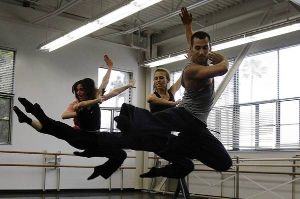 "Miguel Perez (right), Lillian Barbeito (middle/blond hair), Tina Finkelman Berkett (left/dark hair), and Andrew Wojtal (hidden from view) of BodyTraffic rehearse Richard Siegal's ""o2Joy"" at the Loyola Marymount University Dance Department."
