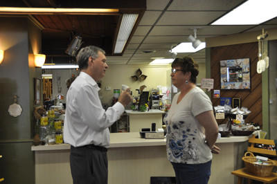 Democratic Pennsylvania governor candidate John Hanger talks to Mary Jo Picklo inside Spice Up Your Life Herbery & Coffee House in Somerset Friday.