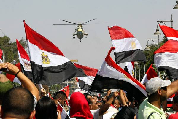 An Egyptian army helicopter hovers as anti-Morsi protesters gather at the presidential palace in Cairo.