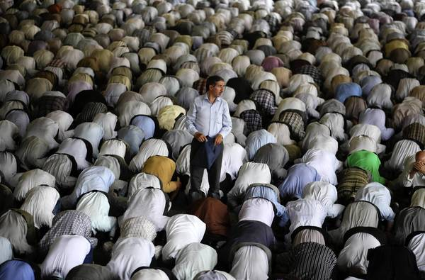 A man stands amid worshipers during Friday prayers in Tehran. As Iran prepares to inaugurate its new, more moderate-sounding president, the Obama administration and Congress are sharply divided on how tough an approach to take on the country's controversial nuclear program.