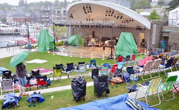 A would-be audience member surveys the scene in rain-soaked East Park in Charlevoix around 7:30 p.m. Friday, July 26 as Venetian Festival officials wait to decide if the evening's events will be called off because of the rain.