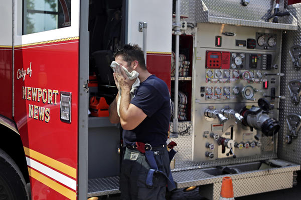 Newport News firefighter/medic Jeremiah Santiago wipes the sweat from his face after securing the scene of a natural gas leak at 39th and Roanoke Friday afternoon.