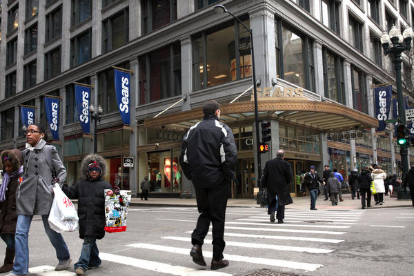 Shoppers and pedestrians walk by the the Sears store on State Street in the Chicago loop in February.