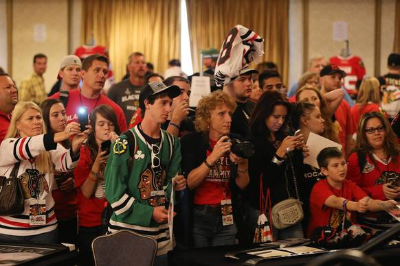 Blackhawks fans hope to get a photo of Patrick Kane following his autograph session during the Blackhawks Convention