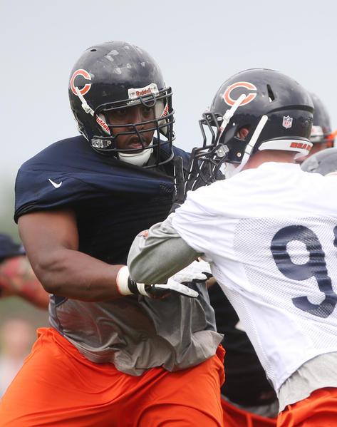 Bears tackle J'Marcus Webb (left) blocks defensive end Shea McClellin during training camp at Olivet Nazarene University.