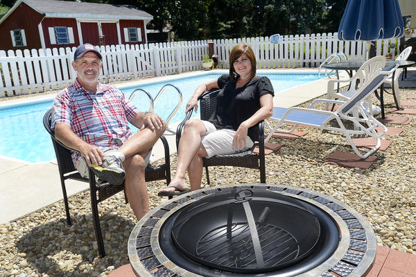 Larry and Cindy Harnish sit poolside at their Maugansville home which they purchased in March and have made many upgrades to.
