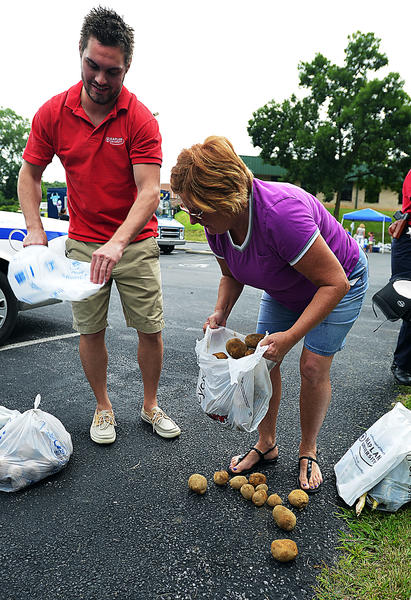 Josh Bowders assists Pat Clark with her bags of potatoes Saturday during Kaplan University's first Community Outreach and Public Safety Day. Food bags contained fresh potatoes, corn and green beans. Clark said she will prepare the food and share with the needy through GloryFire Ministries.