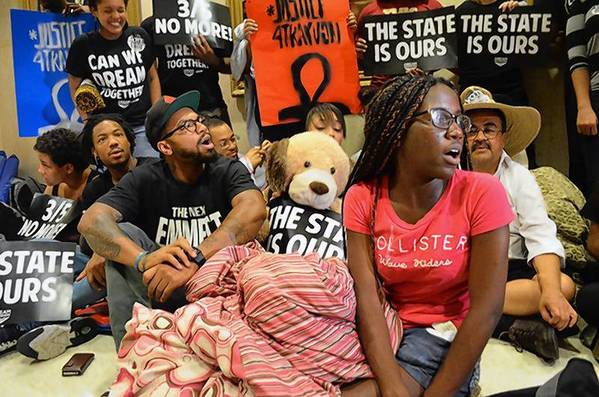 Phillip Agnew (left) and Regina Joseph (right) sit with fellow Dream Defenders in Florida's Capitol.