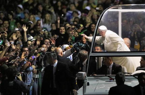 Pope Francis blesses a child from his popemobile as he arrives for a vigil on Rio de Janeiro's Copacabana beach.