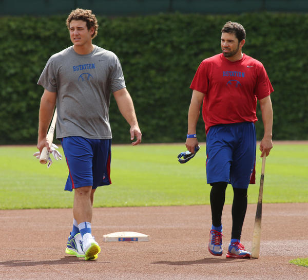 Anthony Rizzo and David DeJesus come in from the outfield batting cage.