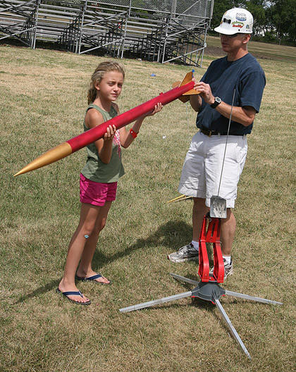 Anna Elsen, 9, of Hecla helps Peter Sykora, a science teacher for the Ellendale (N.D.) School District, set up a model rocket launch Saturday afternoon during Do and Discover Day at the Dickey County (N.D.) Fairgrounds in Ellendale.