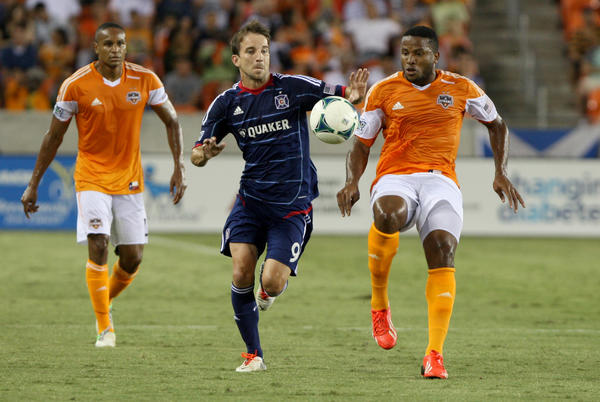 Chicago Fire forward Mike Magee and Houston Dynamo defender Jermaine Taylor battle for the ball during the first half at BBVA Compass Stadium.