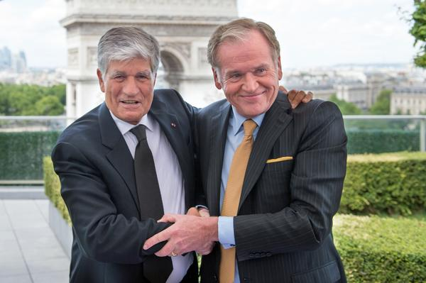 Publicis Group CEO Maurice Levy (L) embraces Omnicom Group CEO John Wren during a press conference in Paris on July 28.