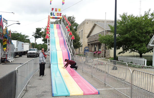 Workers with Arnold Amusments get the Fun Slide ready for action on a bonus day of rides and other Venetian Festival activities in downtown Charlevoix shortly after noon on Sunday, July 28.
