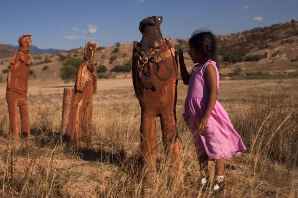 A 2006 photo shows figures sculpted by artist Alejandro Santiago on his ranch outside of Oaxaca City, Mexico. At right is his daughter Alejandra Santiago, then age 4.