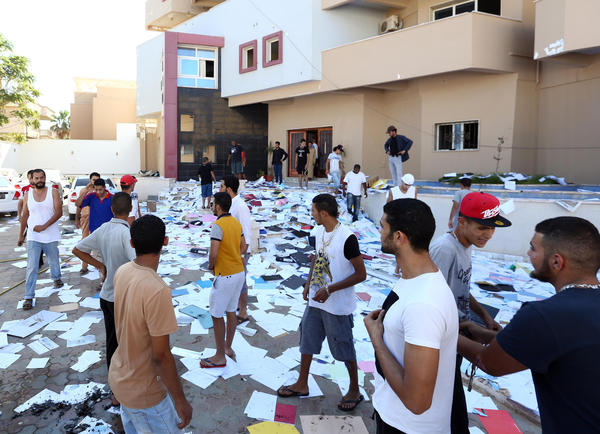Libyan protesters stand amidst scattered documents after ransacking the offices of Muslim Brotherhood-backed Party of Justice and Construction, in the Libyan capital Tripoli on July 27, 2013. Protesters attacked offices of Libya's Muslim Brotherhood as demonstrations sparked by a wave of assassinations in the eastern city of Benghazi turned violent, an AFP correspondent said.