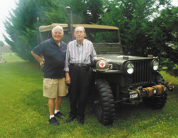 World War II veteran Marvin S. Mann Sr., right, is shown with Guy Whidden, a fellow veteran and paratrooper during the Normandy invasion. They are shown standing next to a restored World War II Jeep provided by Don Blair.