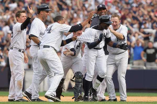 Yankees left fielder Alfonso Soriano is congratulated by teammates after hitting a game-winning single against the Rays during the ninth inning of a game at Yankee Stadium.