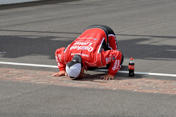 Nascar driver Ryan Newman celebrates after winning the Brickyard 400 by kissing the bricks.